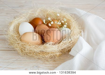 brown and white eggs in a nest on a white wooden table