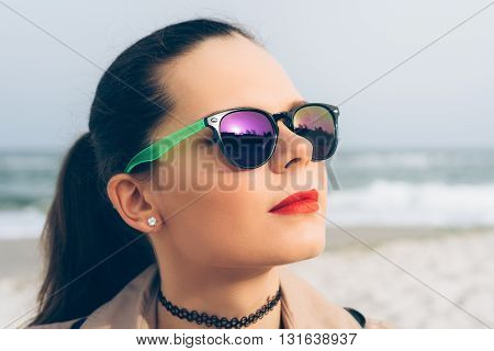 Young woman in sun glasses looks at the sun on the beach in spring