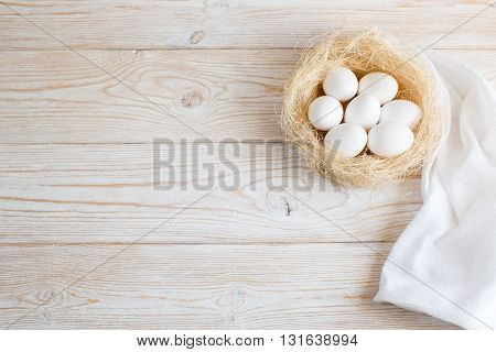 white wooden background with eggs in a nest