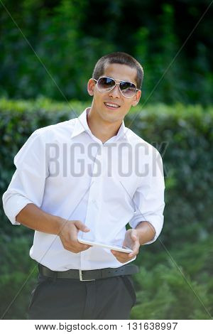 Young Smiling Man In Sunglasses With A Tablet In Hands