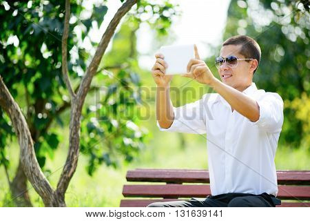 Smiling Young Man In Sunglasses Taking Selfie Through Tablet