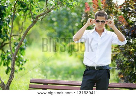Young man in sunglasses in summer park. Nature blurred background