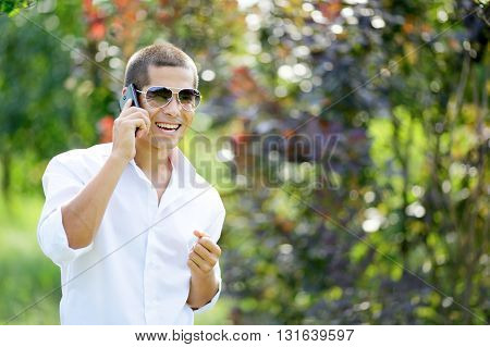 Young Laughing Man Talking On A Mobile Phone