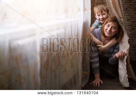 Young mother playing with her little son in the room.