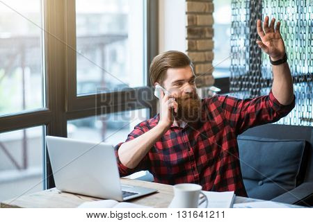 I am here. Pleasant delighted positive bearded man holding his hand up and talking on cell phone while sitting at the table