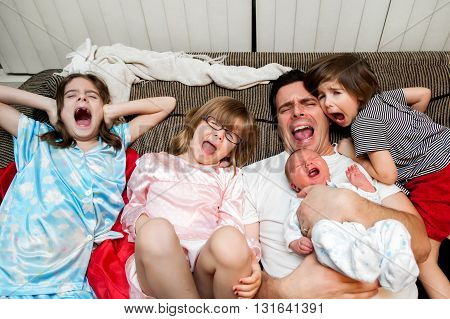 A father, his three daughters, and baby boy lean back on the couch with open mouth screams.  If you can't beat them, join them.