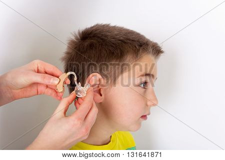 Audiologist putting a hearing aid into young boys ear