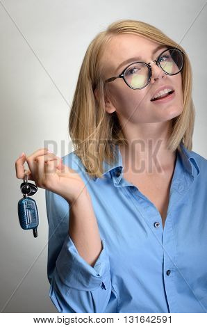 Woman With A Car Keys. Isolated On Grey Background.