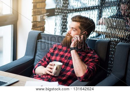 Involved in relaxation. Positive delighted handsome bearded man sitting in the arm chair and drinking coffee while talking on cell phone