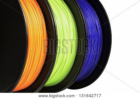 Filament for 3d printing. Bright termoplastic of neon orange green and blue colors. Isolated on white background. Material produced from polylactic (pla) acid. Three reels vertical view. Macro cutout. Concept of new technology for modeling.