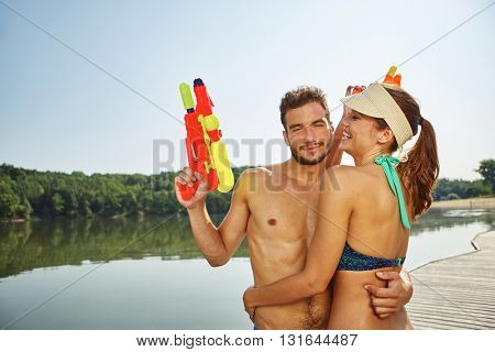 Couple with squirt guns hugging each other in summer