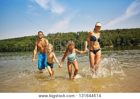 Family and children bathing in the lake and having fun in summer