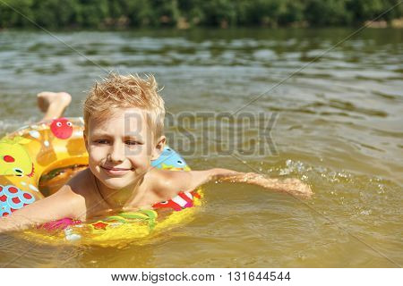 Kid with a floating ring learning how to swim in the water on the holidays