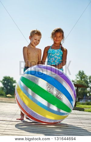 Two happy kids with a beach ball during the summer holidays