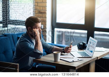 Modern guy. Pleasant handsome bearded man sitting at the table and using cell phone