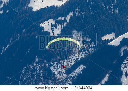 Photo of paraglider in the snowy mountains