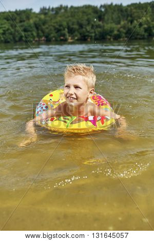 Boy with floating ring learning how to swim in the lake in the summer
