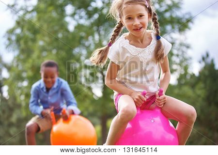 Girl and boy playing with hop ball and having fun