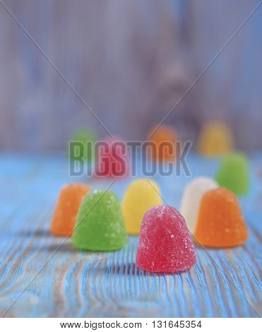 Sweet tasty vibrant candies, wooden background with copyspace