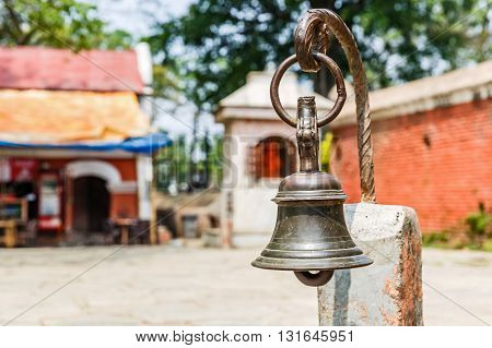 Photo of an ancient bell in a sanctuary courtyard