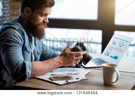 Charged with positivity. Pleasant content bearded man sitting at the table and holding photo camera while feeling glad
