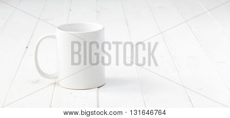 white empty cup on white planked wooden table