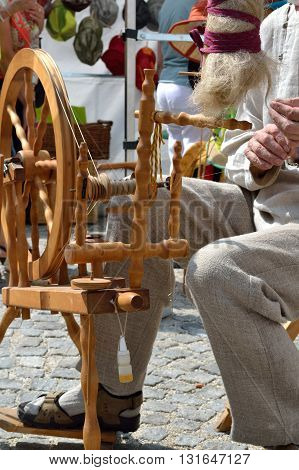 Man sitting at the spinning wheel - closeup