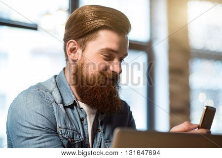 Positive attitude. Cheerful content bearded man smiling and expressing gladness while using cell phone