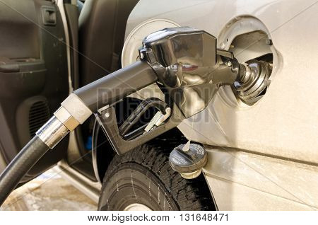 Fuel nozzle in the tank at the gas station. Car refueling concept.