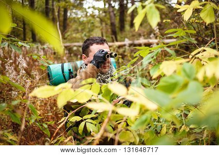 Caucasian man with binoculars at a jungle.