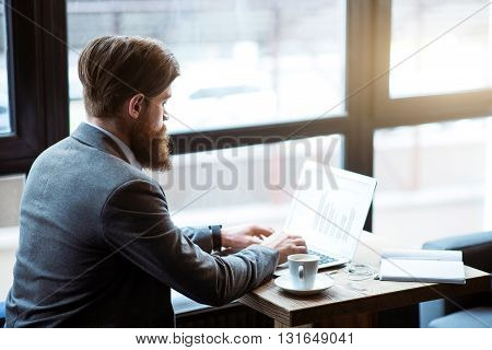 Busy tempo of life. Concentrated bearded man working on the laptop while sitting at the table