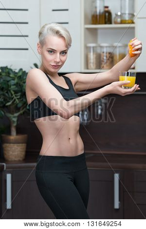 Woman produces orange juice at home wearing sport clothes