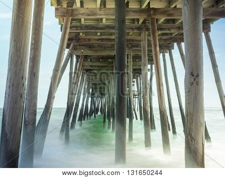 timed exposure of waves coming and going under wooden pier