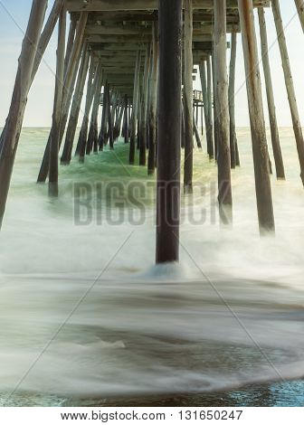 timed exposure, vertical image of waves coming and going under wooden pier