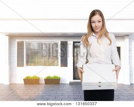 Food delivery concept with businesswoman holding two blank pizza boxes on shop exterior background