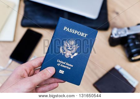 Hand holding american passport over desktop with smart phone camera purse and other items. Traveling concept