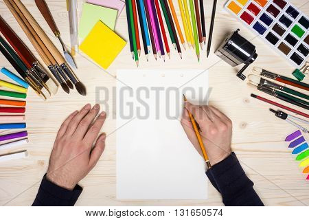 Top view of artist's hands sketching on paper sheet placed on wooden desktop with drawing tools. Mock up