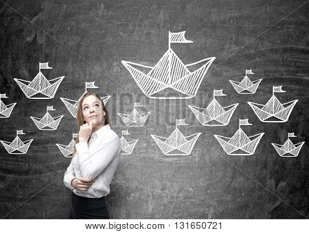 Leadership concept with thoughtful businesswoman standing against chalkboard with paper boat sketches