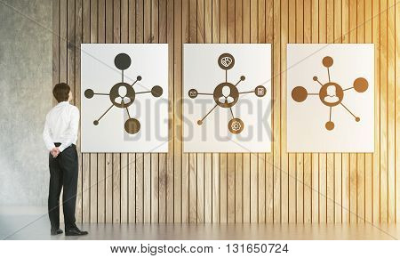 Businessman looking at posters with social network sketches hanging on wooden plank wall. 3D Rendering