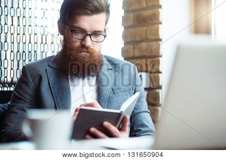 Put it down. Pleasant concentrated bearded man sitting at the table and holding notebook while making notes