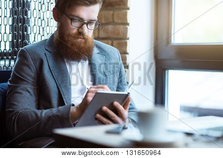 Plan your day. Pleasant glad bearded man sitting at the table and making notes
