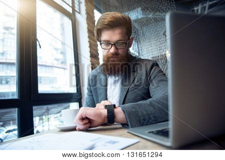 Feel the bio alarm. Pleasant concentrated bearded man sitting at the table while using smart watch