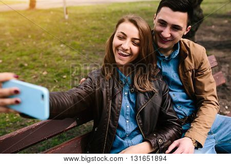 beautiful young couple in the park makes selfie