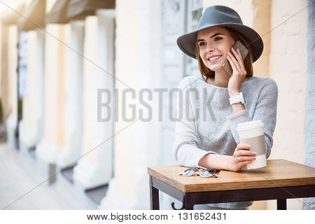 Modern miss. Merry and pleasant young woman speaking per cell phone with her friend while drinking nice coffee in a cafe
