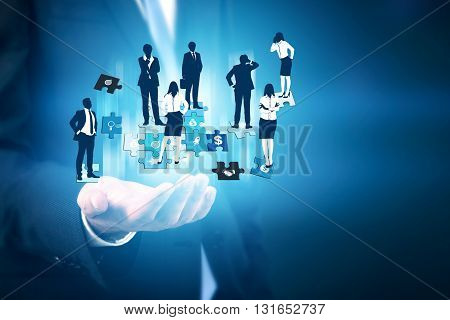 Businessman hand holding abstract image of businesspeople on puzzle pieces. Concept of teamwork and partnership