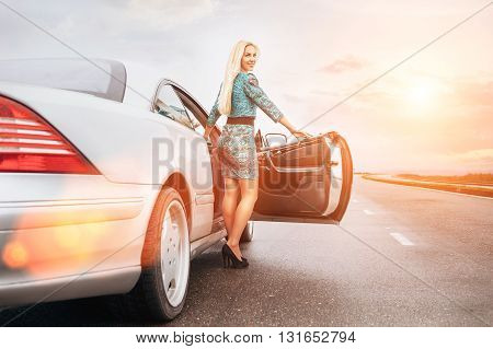 Young blonde woman stay near car on lonely highway