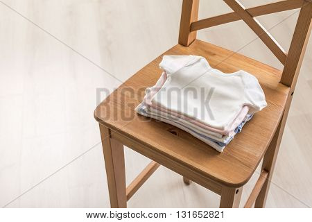 Pile of baby shirts on wooden chair