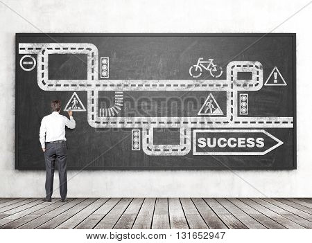 Businessman drawing road to success sketch on chalkboard hanging in room with concrete wall and wooden floor