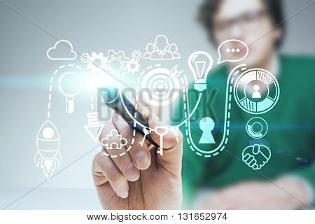 Startup concept with blurry young man drawing abstarct sketch with marker on light grey background