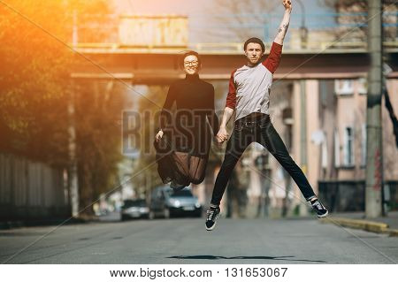 Beautiful young couple jumping in the street